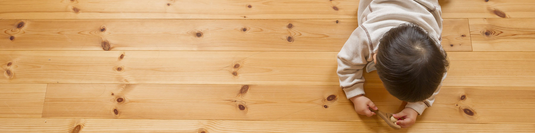 Kid Playing With Toy On Hardwood Flooring